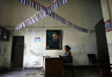 HAV101 - A clerk sits under a portrait of Cuba's President Fidel Castro at an office of the Cuban...