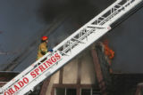 (DLM7870) -  Flames shoot from the top of the Castle West Apartments as a firefighter fights a...