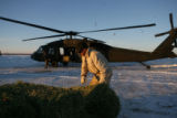 Jack Martin, cq, of Larmar, picks up a bail of hay to load on a an Army Blackhawk helicopter...