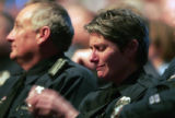 An officers from the Aurora Police department wipes her tears  as she listens joins other officers...