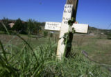 A cross marks the final spot where a woman was killed after being dragged behind a car in...