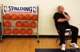 Denver Nuggets head coach George Karl, right, watches his team practice while sitting next to a...