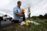 Sandi Berg(cq) places flowers around a memorial near her home on Surrey Road in Douglas County...