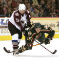 MNAH104 - Minnesota Wild right wing Mattias Weinhandl (18), of Sweden, swats away the puck and...