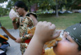 Adam Salazar, 8, CQ, right, learns how to blow a conka shell from family friend Beto Maestas, 18,...
