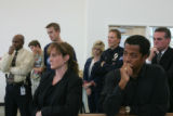 Friends, co-workers and family of slain Aurora Police Officer Mike Thomas listen as the officer's...