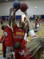 Harlem Globetrotter Herb Evans, plays keep-away from students during recess at  Pinnacle Charter...