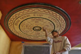 Cesar Perez (cq) fills in the screws that holds this painting, by Dymphna Curry (cq) to the...