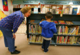 Judy Herbet offers help to kindergartner Joe Castillo (cq), 5, in the library at Eisenhower...