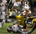 The Denver Broncos Demetrin Veal (#97, DT) and John Lynch (#47, S) combine on the tackle of the...