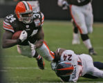 Former Denver Bronco, Reuben Droughns, left, is brought down by  Cleveland Browns cornerback Champ...