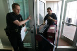 (DLM4441) -  A Denver police officer holds the door for Sean Davis and Tony Centeno with Alliance...