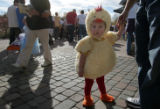 Chandler Guthrie, 19 months old, dressed as Chicken Little waits for goodies with her father from...