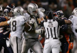 (RMN1079) -  Head linesman Jim Mello, #48, separates Oakland Raiders Robert Gallery, #76, and ...