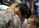 Jackie DePriest, cq, center, holding her son Tyler, 10 months, greets her husband Sgt. Michael...