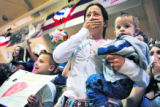 Jackie DePriest, cq, center, holding her son Tyler, 10 months, holds back tears as she watches her...