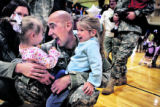 Carlessa Shulz, cq, far left, with daughters Brilynn, cq, 1, and Breann, cq, 3, greet Spc. Eric...