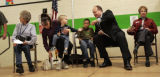 Aurora Board of Education President Mark Cook (second from right) reaches past fifth grader Marco...