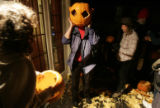 Friends finish hollowing out pumpkins to where on their heads before streaking down Boulder's...
