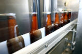 (DLM0870) -  Bottles speed along a conveyor after being filled with beer and capped at the...