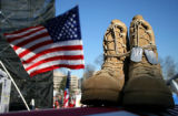 Boots of a fallen soldier were laid on top of a casket and displayed on the a main stage during...