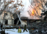 Firefighters battle a house fire at 7820 Larkwood Street in Commerce City early Thursday January...