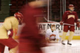DU goalie Glenn Fisher stretches while fellow players skate around during practice at the Magness...
