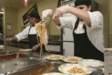 Leticia Ruiz, left, dishes sauce and meatballs while Arcelya Gaytan, lays in the noodles during a...