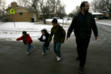 (DLM6306) -  Eric Hayes walks to his car with his two kids Dylan, 4, far left, and Donovan, 10,...