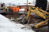 Workers stand over a 20 foot by 20 foot sinkhole which developed early  Thursday in the 3900 block...