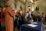 BG0164 Governor Bill Ritter signs his first bill into law, Senate Bill 1, while flanked by the...