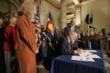 BG0181 Governor Bill Ritter signs his first bill into law, Senate Bill 1, while flanked by the...