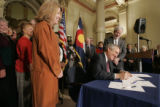 BG0194 Governor Bill Ritter signs his first bill into law, Senate Bill 1, while flanked by the...
