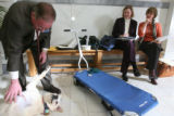 Jerry Braden, Governmental Consultant, gives Boone, dog, a scratch as purple, Tami Struessel, PT,...