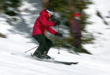 A skier blows by a boarder stopped on the side of the run near the bottom of the Mozart run at...