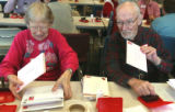L to R: Erna (cq) and Neil Menczer (cq) stamp envelopes during the 61st year of the Loveland...