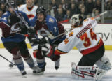 Colorado Avalanche players Ben Guite, left, and Ken Klee, middle, go up against Calgary Flames...