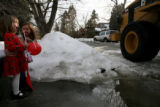 Kiley Petracek, 3, and her friend Neave Fleming, 5, react to a passing tractor as it remove the...
