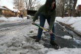 Park Hill resident, Stephanie Grilli, cq, removes ice from the curbside of the street in front of...