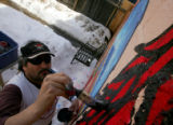 "[JPM203] Amid melting, slushy snow, Mark G. Martinez Luna paints a mural called ""A Pleasant..."