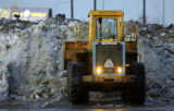 A front-end loader moves piles of snow and ice around a parking lot near Coors Field in Downtown...