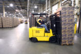 (DLM0100) -  Pallets of boxes filled with empty bottles are unloaded from trucks and moved onto...