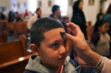 Luis Arrieta (cq), 8, receiives ashes on hiis forehead during morning mass for Ash Wednesday at...
