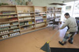 Mark Sazatino, (cq), cleans up an agave nectar spill near the new display shelves as you enter the...