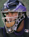The green eyes of Colorado Rockies catcher Alvin Colina stare at a pitching machine as he works on...