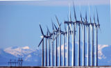 COEA105 - The Rocky Mountains can be seen in the distance as wind mills generate electricity at...