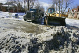 A front-end loader prepares to clear some ice and snow into a dumptruck near 10th Avenue and...