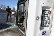 (DLM0783) -   Denver Police officer Dan McNulty scoops up glass from the road next to a white...