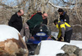 Jefferson County Sheriff Deputies and members of the Alpine Search and Rescue group load the body...