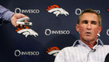 A reporter tapes Denver Broncos coach Mike Shanahan as he answers other reporters' questions at...